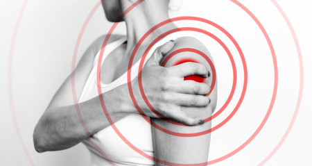 Acute shoulder pain. Hand touch the painful point. Pain area highlighted in red. Healthcare and medical concept, black and white image Reklamní fotografie