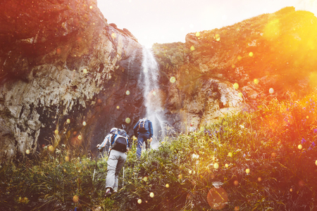 Group Of Tourists Walking Uphill To Waterfall With Sunlight. Travel Adventure Outdoor Concept