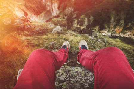 Male traveler legs of a traveler sitting on a rock against a cliff, point of view shot. Travel Lifestyle Adventure Vacations Concept