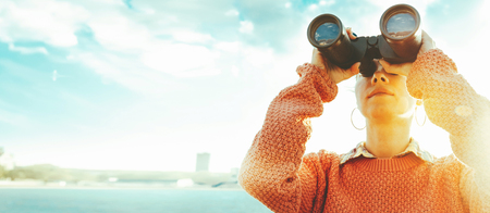 Young girl looks through binoculars at a sunny and sunny day. Travel Concept