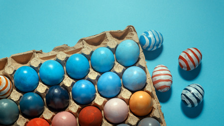 Colorful Easter eggs lie in a row on a blue background, top view with copy-space