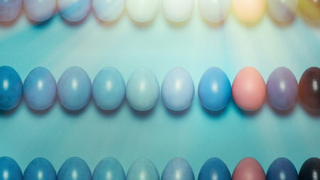 Creative Easter concept. Colored Easter eggs of a blue gradient in a row on a blue background. View from above