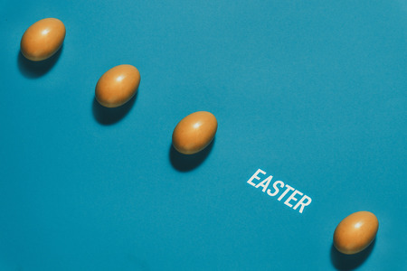 Pattern of Yellow Easter eggs on a blue background. Creative concept