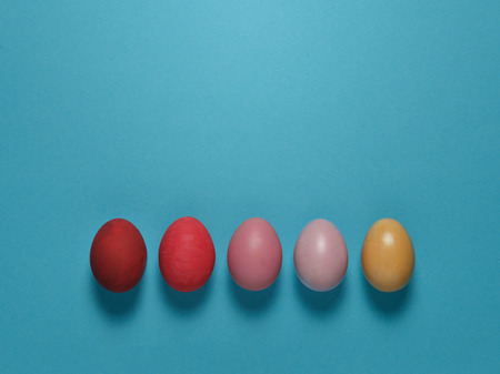 Colored Easter eggs lie in a row on a blue background, top view