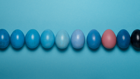 Creative Easter concept. Colorful Easter eggs on a blue background. View from above