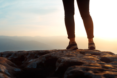 Unrecognizable young success woman hiker legs on mountain peak rock, rear view.  Concept achieving goal, beginning of the path, travel,  adventure, sport 写真素材