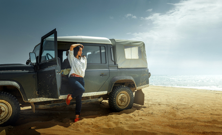 Attractive Young Woman Traveler Enjoying The Sea View, Leaning Back On a Classic Car SUV