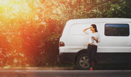 Beautiful young girl travels in a camping van, looks away and enjoys a mug of hot coffee or tea with copy-space. Road adventure concept and lifestyle Фото со стока