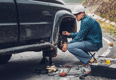 Male traveler is fixing a car. The concept of a road adventure, overcoming difficulties on the way