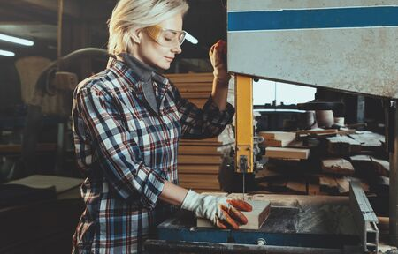 Middle aged woman working with a drill in workshop. Concept of woman in a male-dominated profession, nontraditional gender roles, gender equality, image of femininity