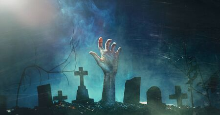 Zombie Hand Rising Out Of A Graveyard In Spooky Night. Horror Halloween Holiday event banner background concept. Film grain and scratches