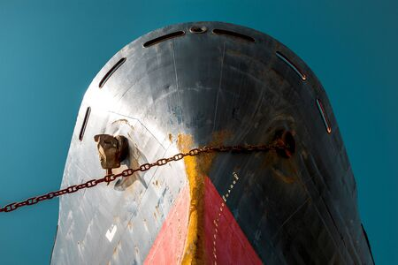 Ship's nose with red waterline against the blue sky. World shipping freight concept