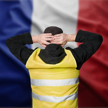 Yellow vests protests. A young man stands with his back and holds his hands on his head as a sign of obedience. The concept of revolution and protest, the struggle for equal rights, the electoral movement Foto de archivo