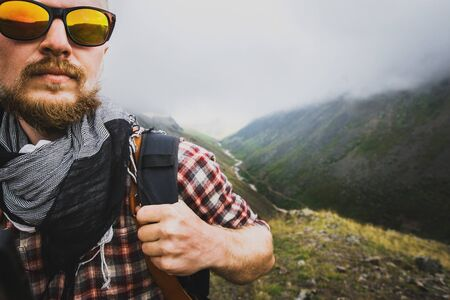 Young male traveler with backpack and in sunglasses climbs a mountain on foggy morning, close up. In background is estuary