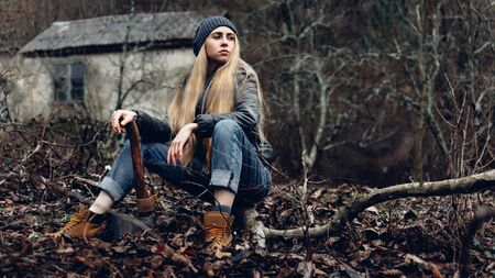 Attractive Girl Resting In Forest Holds An Ax In Hands. Bushcraft Survival Concept