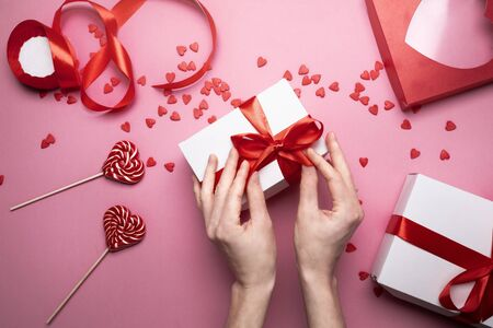 Female Hands Packed Gift For Valentines Day On Pink Background, Top view Banque d'images - 138463053