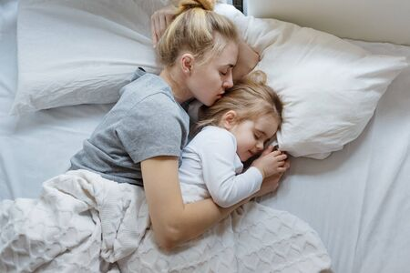Young mother and little daughter sleep in bed, top view with copy-spase. Concept of security, protection, comfort, family values, single-parent family