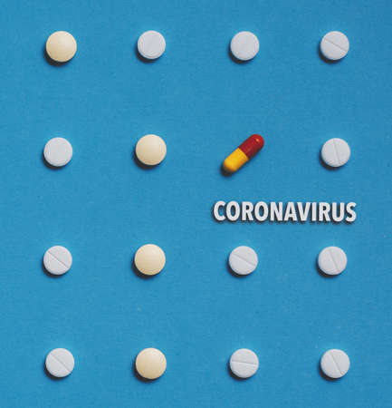 Outbreak of coronavirus infection 2019-nCoV. Vaccine development drugs, pills with text on blue background concept Standard-Bild