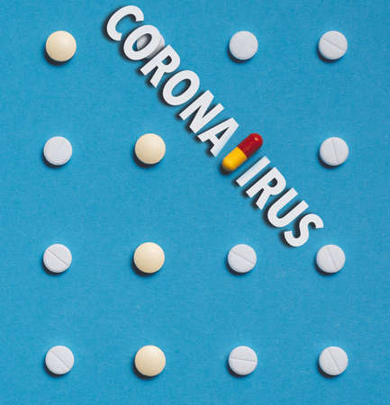 Outbreak of coronavirus infection 2019-nCoV   concept. Vaccine development drugs, Colored Pill On Blue Background