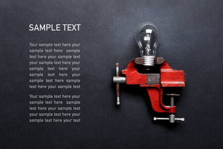 Light bulb clamped in mechanical hand vise on grey background with copy space and sample text. Creative design concept