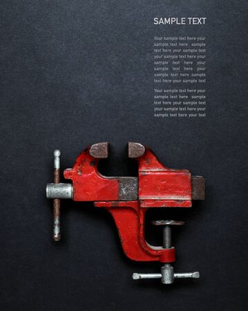 Metalwork tool - red vintage mechanical hand vise clamp on grey background with copy space and Sample text, top view