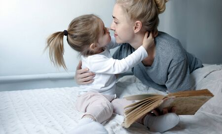 Young mother with small daughter cuddles and looks into each others eyes, sitting on the bed. Concept Love, Tenderness in family