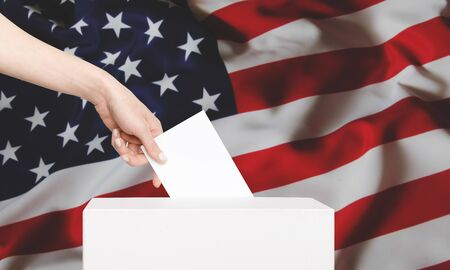 Female Voter Putting Ballot into Voting Box On Background US Flag. Concept of Freedom Democracy With copy-space Standard-Bild