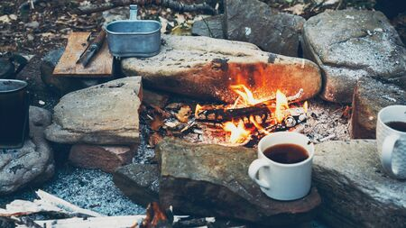 Hot coffee or tea in mugs near campfire. Hiking tourism concept