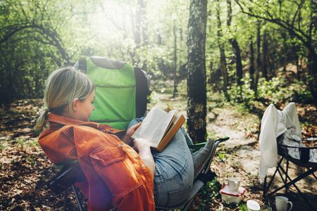 Finding solitude in wilderness concept. Young woman resting in forest, sitting in camp chair and reading book