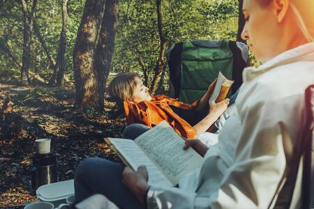 Two young girls relax on camping and read books