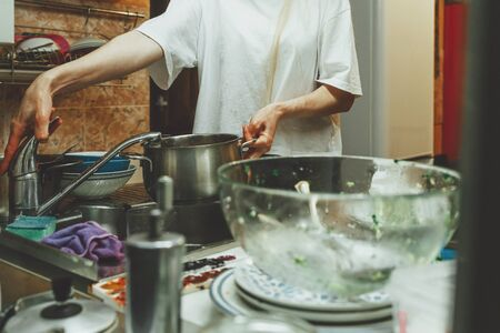 Unrecognizable woman washes dishes in kitchen