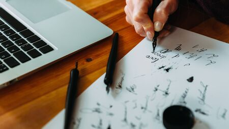 Unrecognizable girl trains in calligraphy and lettering, close-up