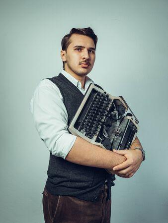 Portrait Of Man Holding Typewriter