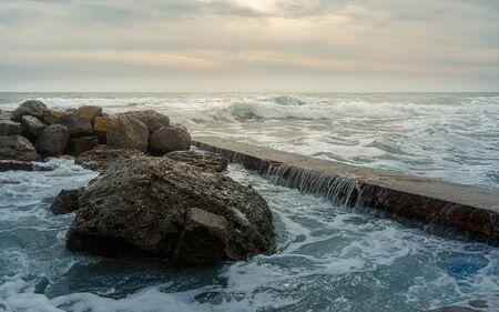 Foamy waves crash on rocky shore