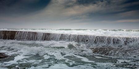 White foam waves roll through breakwater Standard-Bild