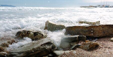 Foamy waves roll on rocky beach Standard-Bild