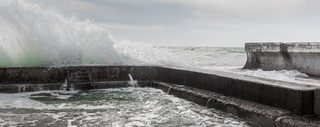 Waves crash against breakwater, forming splashes