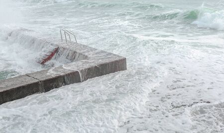Waves crashing on breakwater with red stairs, turning into milk foam