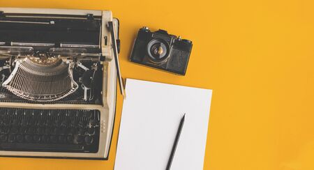 Typewriter, Retro Film Camera, Sheet Of Paper And Pencil On Yellow Background, Top View With Copy-space. Creative concept