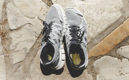 Old Running Shoes On Stone Surface Standard-Bild