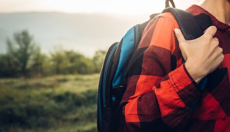 Unrecognizable Young Woman Traveler In Red Plaid Shirt With Backpack On Landscape Background. Scout Travel Adventure Concept