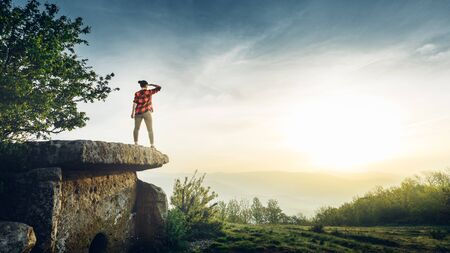 Woman Traveler Stands On Ancient Megalith And Looks Into Distance. Scout Travel Adventure Concept