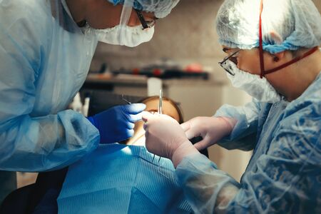 Dentist And Assistant Treat Teeth Of Little Girl