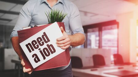 Unrecognizable Male Office Worker Holding A Box With Inscription Need A Job. Unemployment Concept