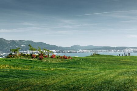 Green Golf Course With Mountains And Sea Standard-Bild
