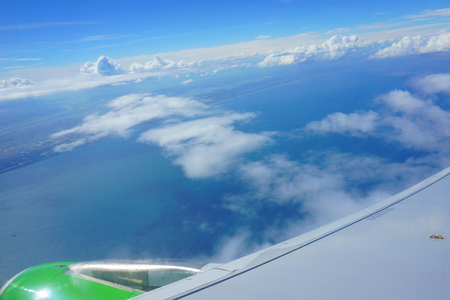 view from airplane porthole. blue sky, sea, coast, wing of plane Archivio Fotografico