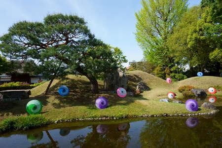 Ashikaga, Tochigi / Japan April 29, 2019: Ashikaga Gakko is Japan's oldest academic institution. Landscape, pond, colorful umbrellas