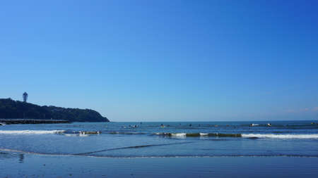 People surfing on sea waves under blue sky. Katase Nishihama beach is one of Japan's most popular beaches. Beach next to Enoshima Island