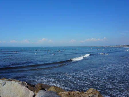People surfing on sea waves under blue sky. Katase Nishihama beach is one of Japan's most popular beaches