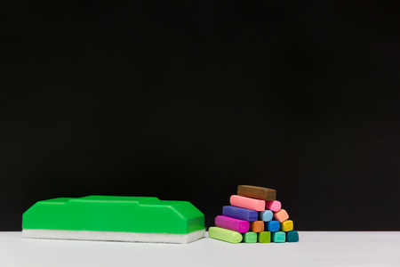 Colorful of the chalk pastels and green blackboard eraser with black background